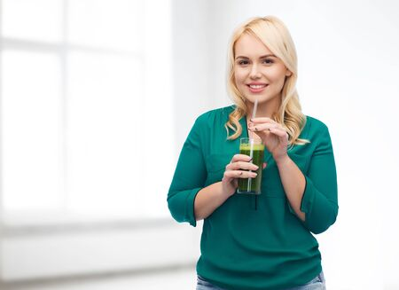 green vegetable: healthy eating, vegetarian food, diet, detox and people concept - smiling young woman drinking green vegetable juice or smoothie from glass over white room background