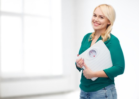weight loss, diet, slimming, plus size and people concept - smiling young woman holding scales over white room background Stock Photo