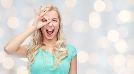 ok hand: fun, emotions, expressions and people concept - smiling young woman or teenage girl making ok hand gesture over holidays lights background