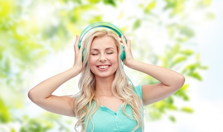green technology: technology, summer and people concept - happy young woman or teenage girl with headphones listening to music over green natural background