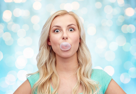 emotions, expressions and people concept - happy young woman or teenage girl chewing gum over blue holidays lights background