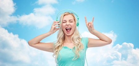 music, technology and people concept - happy young woman or teenage girl with headphones singing song and showing rock gesture over blue sky and clouds background Stock Photo