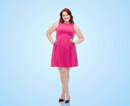 女性、ジェンダー、肖像画および人々 のコンセプト - 幸せな若いプラス サイズ女性が青い背景にピンクのドレスでポーズを笑顔