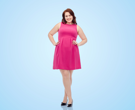 female, gender, portrait and people concept - smiling happy young plus size woman posing in pink dress over blue background Standard-Bild