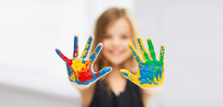 children drawing: education, school, art and painitng concept - little student girl showing painted hands