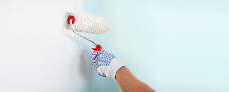wall paint: repair, building and home concept - close up of male in gloves painting wall with roller Stock Photo