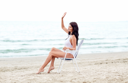 relaxing beach: summer vacation, tourism, travel, holidays and people concept - smiling young woman sunbathing in lounge or folding chair pointing finger on beach