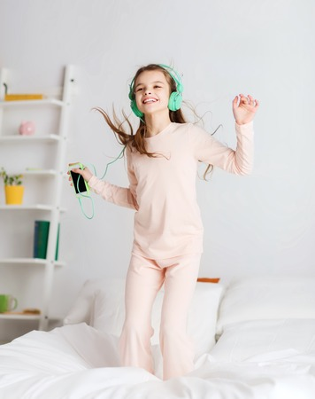 handphone: people, children, pajama party and technology concept - happy smiling girl in headphones jumping on bed with smartphone and listening to music at home