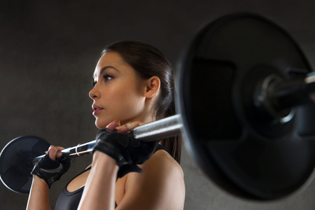 weightlifting equipment: sport, fitness, bodybuilding, weightlifting and people concept - young woman with barbell flexing muscles in gym Stock Photo