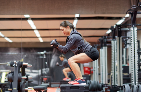 squats: fitness, sport, exercising and people concept - woman doing squats on platform in gym Stock Photo