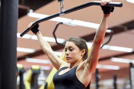 arm muscles: sport, fitness, bodybuilding, lifestyle and people concept - woman flexing arm muscles on cable machine in gym