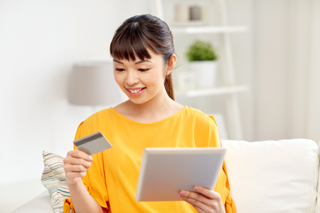 people, internet bank, online shopping, technology and e-money concept - happy asian young woman sitting on sofa with tablet pc computer and credit card at home