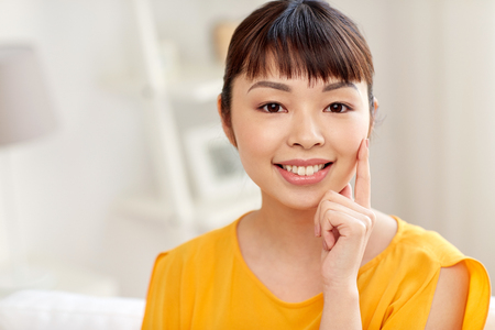 people, race, ethnicity and portrait concept - happy asian young woman or teenage girl face at home