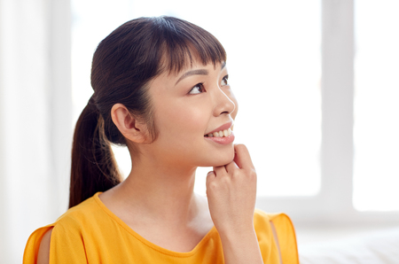 decent: people, race, ethnicity and portrait concept - happy asian young dreaming woman or teenage girl face at home Stock Photo