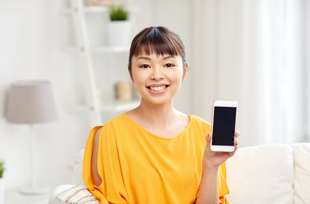 showing: people, technology, communication and leisure concept - happy young asian woman sitting on sofa and showing smartphone blank screen at home Stock Photo