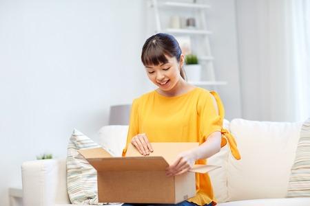 la gente, la entrega, el comercio, el transporte y el concepto de compra - mujer joven asiática feliz con la caja de cartón del paquete en casa