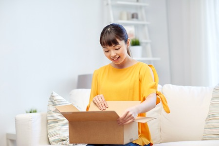 people, delivery, commerce, shipping and shopping concept - happy asian young woman with cardboard parcel box at home Stockfoto