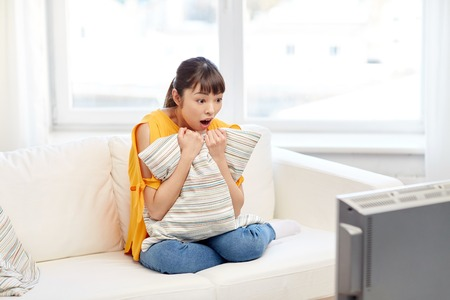 scared woman: television, leisure and people concept - asian young woman watching tv at home
