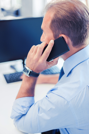 telephone salesman: business, communication and technology concept- businessman with smartphone in office
