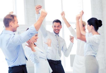 Obraz szczęśliwy zespół biznesowych świętuje zwycięstwo w biurze