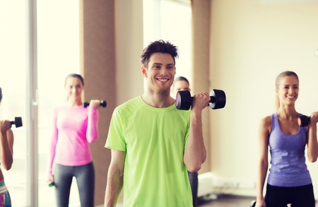 working: fitness, sport, training, gym and lifestyle concept - group of smiling people working out with dumbbells flexing muscles s in gym