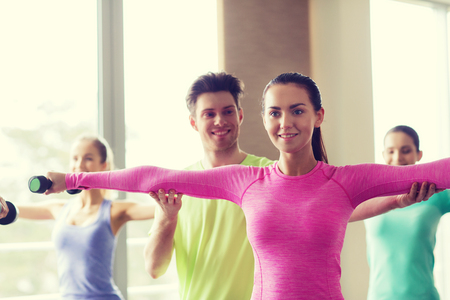 fitness gym: fitness, sport, training, gym and lifestyle concept - group of smiling people working out with dumbbells flexing muscles s in gym