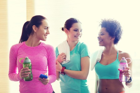 water bottles: fitness, sport, training, gym and lifestyle concept - group of happy women with bottles of water in gym