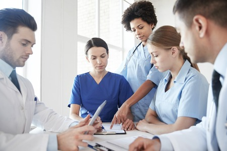 Krankenhaus, medizinische Bildung, Gesundheitswesen, Menschen und Medizin-Konzept - Gruppe von Ärzten mit Tablet-PC Computer Sitzung im medizinischen Büro