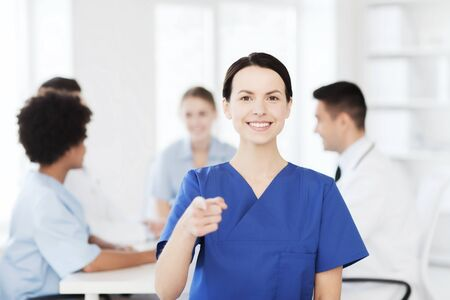 medics: clinic, profession, people and medicine concept - happy female doctor or nurse over group of medics meeting at hospital pointing finger to you