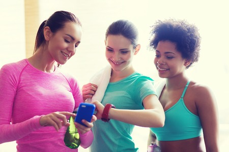 women sport: fitness, sport, training, gym and lifestyle concept - happy women showing time on wrist watch in gym Stock Photo