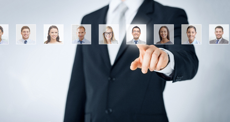 human resources, career management, recruitment and success concept - man in suit pointing to of many business people portraits