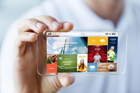 ビジネス、技術と人のコンセプト - 画面で透明なスマート フォン ニュース web ページの表示を押しながら男性の手のクローズ アップ