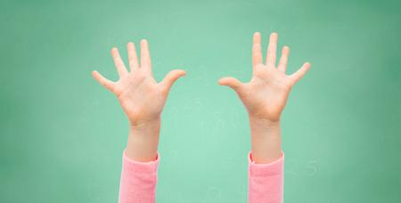 Concepto de las personas, de la infancia, de gestos, de educación y partes del cuerpo - cerca de las pequeñas manos del niño planteadas a lo largo de la escuela verde fondo de la tarjeta de tiza Foto de archivo - 60340468
