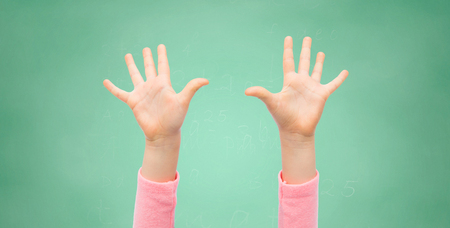 10 fingers: people, childhood, gesture, education and body parts concept - close up of little child hands raised up over green school chalk board background Stock Photo