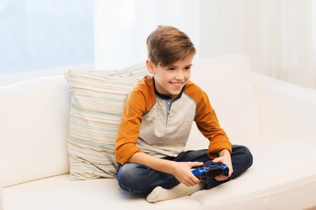 niños jugando videojuegos: ocio, los niños, la tecnología y el concepto de la gente - muchacho sonriente con joystick jugando videojuegos en el hogar