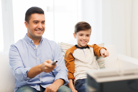 entertainment concept: family, people, technology, television and entertainment concept - happy father and son with remote control watching tv at home