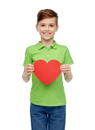 forme et sante: enfance, l'amour, la charité, les soins de santé et les gens concept - garçon souriant heureux t-shirt de polo vert tenant en blanc en forme de coeur rouge Banque d'images