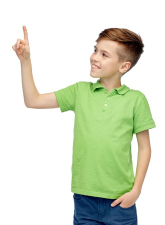 childhood, fashion and people concept - happy smiling boy in green polo t-shirt pointing finger up
