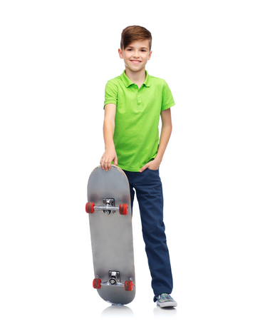 childhood, leisure, school and people concept - happy smiling boy with skateboard Stock Photo