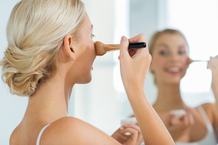 powder room: beauty, make up, cosmetics, morning and people concept - close up of smiling young woman makeup brush and powder foundation looking to mirror at home bathroom Stock Photo