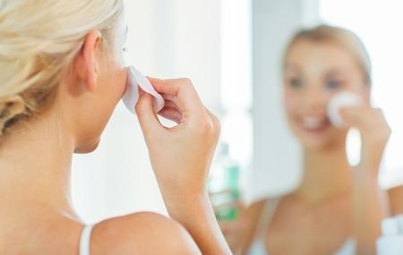 krása, péče o pleť a lidé koncept - zblízka usmívající se mladá žena čištění obličeje s bavlněným disku a pleťová voda v koupelně
