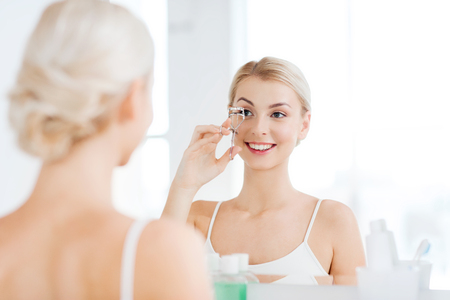lifestyle looking lovely: beauty, make up, cosmetics, morning and people concept - smiling young woman with curler curling eyelashes and looking to mirror at home bathroom