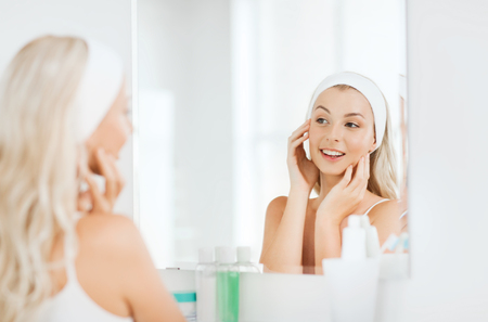 hairband: beauty, skin care and people concept - smiling young woman in hairband touching her face and looking to mirror at home bathroom