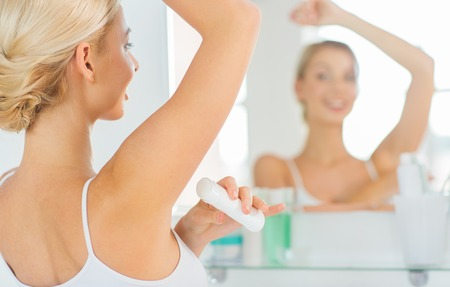 beauty, hygiene, morning and people concept - close up of smiling young woman applying antiperspirant or stick deodorant and looking to mirror at home bathroom Stock Photo