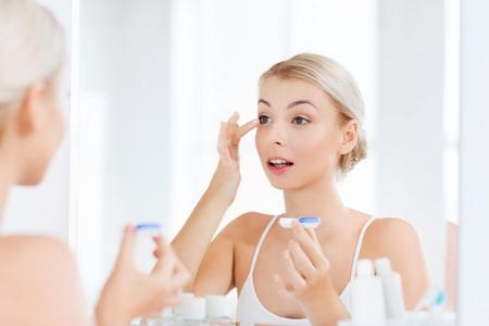 Schönheit, Sehen, Sehvermögen, Ophthalmologie und Menschen Konzept - junge Frau, die auf Kontaktlinsen am Spiegel im Haus Badezimmer