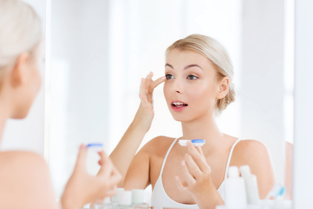 beauty, vision, eyesight, ophthalmology and people concept - young woman putting on contact lenses at mirror in home bathroom Stockfoto