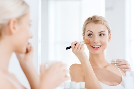 powder room: beauty, make up, cosmetics, morning and people concept - smiling young woman makeup brush and powder foundation looking to mirror at home bathroom Stock Photo