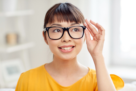 living wisdom: people, education, vision and portrait concept - happy asian young woman or teenage student girl in glasses at home Stock Photo