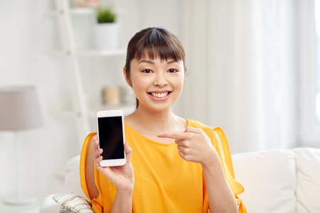 people, technology, communication and leisure concept - happy young asian woman sitting on sofa and showing smartphone blank screen at home Stock Photo