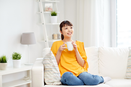 happy asian people: people, drinks and leisure concept - happy asian woman sitting on sofa and drinking tea from cup or mug at home